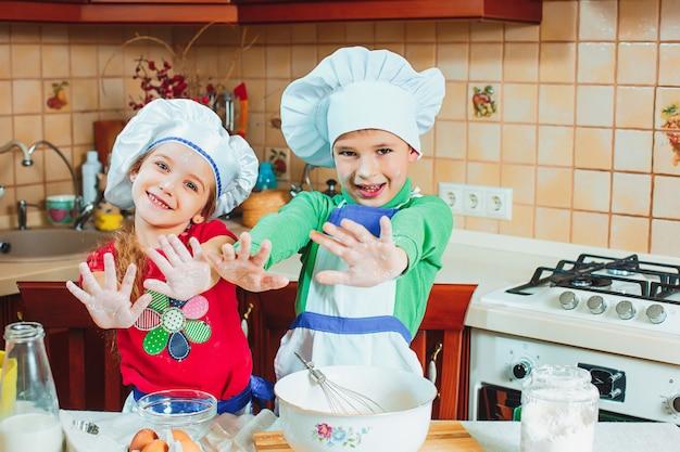 Familia feliz niños divertidos están preparando la masa, hornear galletas en la cocina