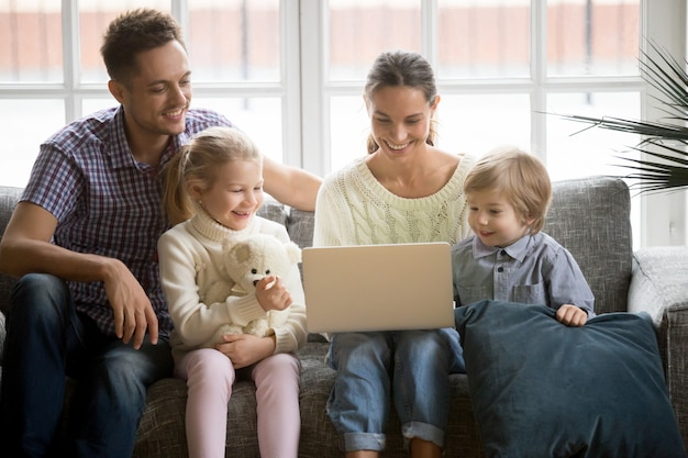 Familia feliz con niños divirtiéndose usando laptop en sofá