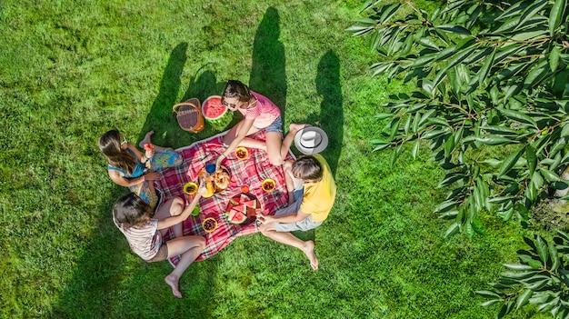Familia feliz con niños haciendo un picnic en el parque, padres con niños sentados en el césped del jardín y comiendo comidas saludables al aire libre, vista de aviones no tripulados desde arriba, vacaciones familiares y concepto de fin de semana
