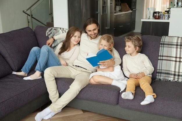 Familia feliz con los niños leyendo libro juntos sentados en el sofá
