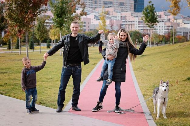 Familia feliz con niños pequeños y perro husky en el parque, otoño al aire libre
