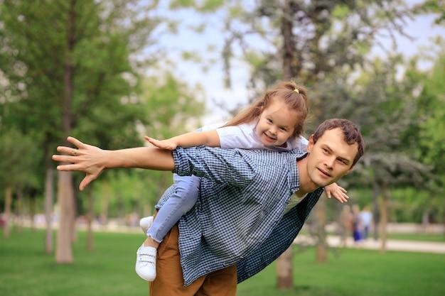 Familia feliz, padre e hija están jugando en el parque de verano