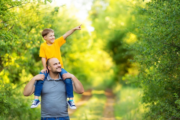 Familia feliz: padre e hijo caminan en la naturaleza en verano. el hijo está sentado en la espalda de su padre.