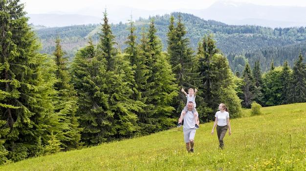 Familia feliz: padre con hijo en hombros y madre caminando sobre un campo verde contra el bosque de coníferas y las montañas.