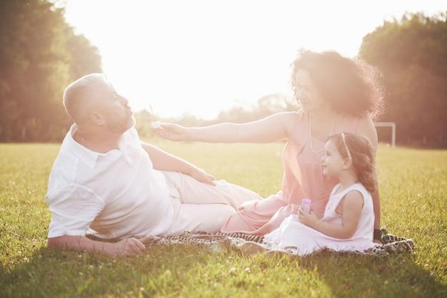 Familia feliz, padre de madre e hija de bebé en la naturaleza al atardecer