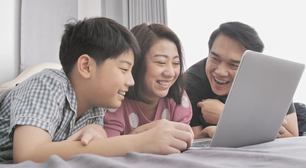 Familia feliz padre madre e hijo mirando en la computadora portátil.