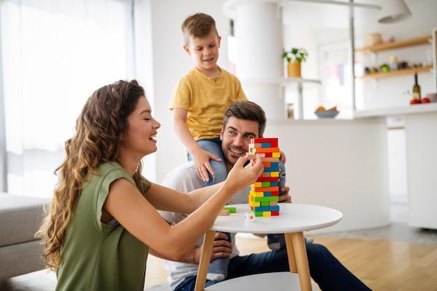 Familia feliz con padres e hijo jugando con bloques de colores en casa