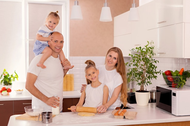 Familia feliz, papá, mamá e hijas cocinan en la cocina, amasan la masa y hornean galletas.