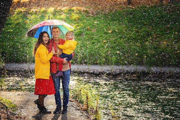 Familia feliz bajo el paraguas esconderse de la lluvia.