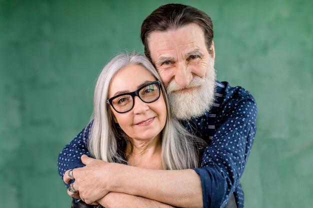 Familia feliz, pareja de ancianos enamorados, de pie sobre fondo verde