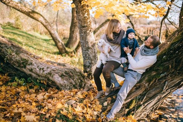 Familia feliz pareja con su pequeño niño y cachorro pasar tiempo en el parque de otoño.
