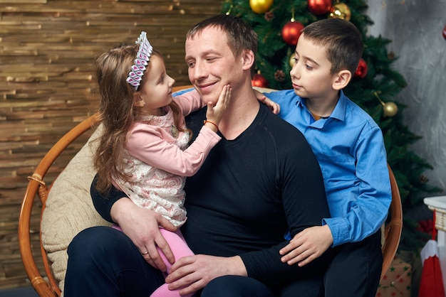 Familia feliz pasa tiempo juntos en vacaciones de invierno en casa junto a la chimenea cerca del árbol de navidad con regalos. linda niña y niño con su padre en la silla en el árbol de navidad.