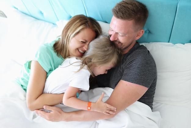 Familia feliz pasar tiempo juntos en casa en la cama.