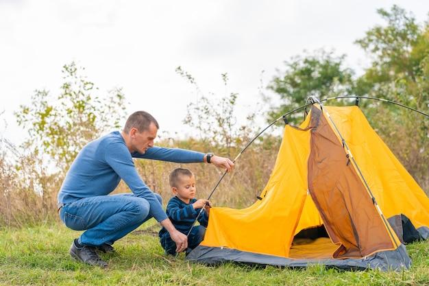 Familia feliz con pequeño hijo configurar tienda de campaña. infancia feliz, viaje de campamento con los padres. un niño ayuda a armar una carpa.