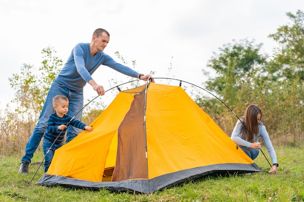 La familia feliz con el pequeño hijo instaló la tienda de campaña. infancia feliz, viaje de campamento con los padres. un niño ayuda a armar una carpa.