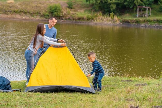 La familia feliz con el pequeño hijo instaló la tienda de campaña. infancia feliz, viaje de campamento con los padres.