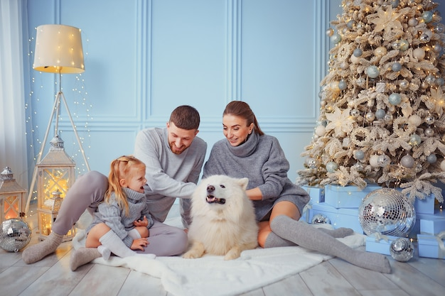 Familia feliz con perro cerca del árbol de navidad.