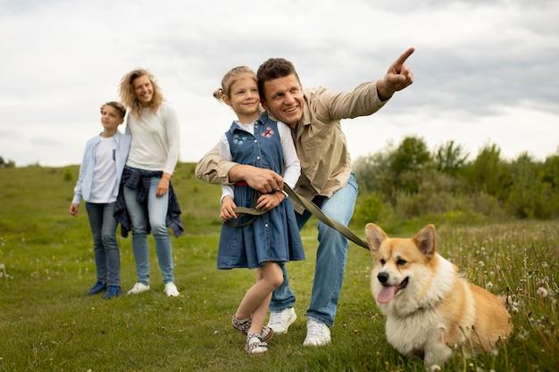 Familia feliz con perro en la naturaleza tiro completo