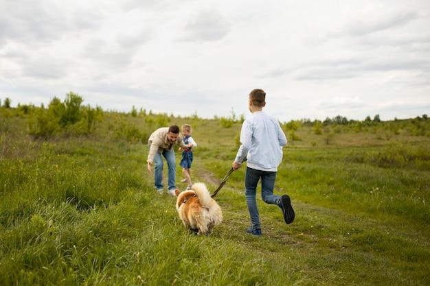 Familia feliz con perro en la naturaleza