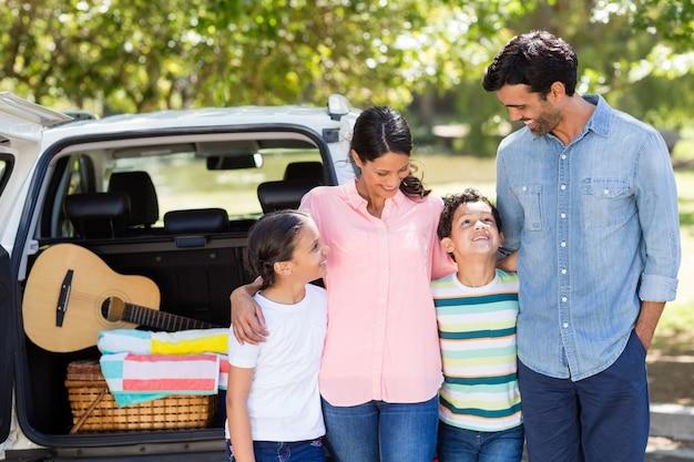 Familia feliz en un picnic de pie junto a su automóvil