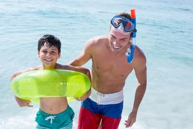 Familia feliz con pie de anillo de natación en el mar