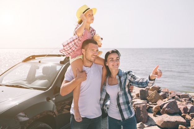 Familia feliz de pie cerca de un coche en la playa. familia feliz en un viaje por carretera en su coche. papá, mamá e hija viajan por el mar, el océano o el río. paseo de verano en automóvil