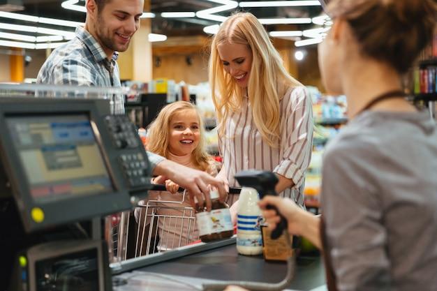 Familia feliz de pie en el mostrador de efectivo