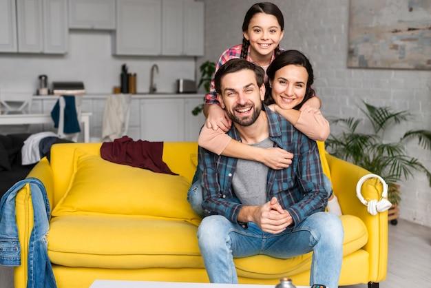 Familia feliz en una pila y papá sentado en el sofá