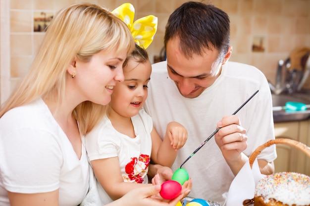 Familia feliz pintando huevos de pascua en la mesa de la cocina