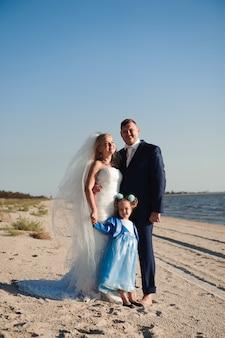 Familia feliz en una playa al amanecer - niño madre y padre