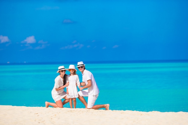 Familia feliz en la playa blanca