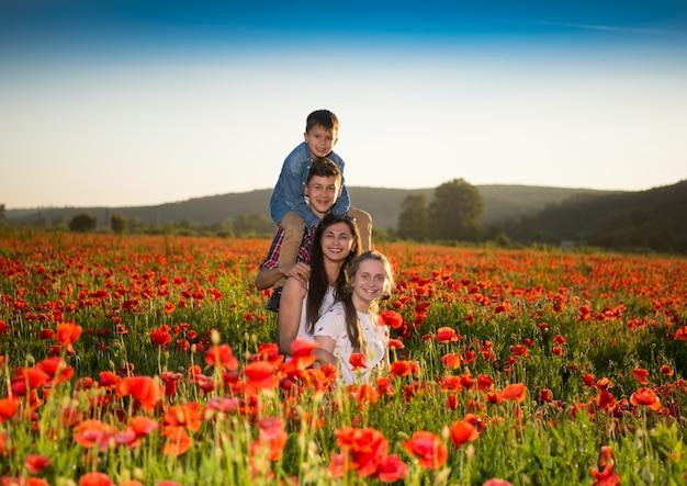 Familia feliz posando en el campo de amapolas al atardecer. día soleado de verano