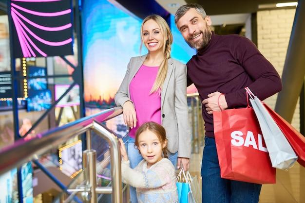 Familia feliz posando en el centro comercial