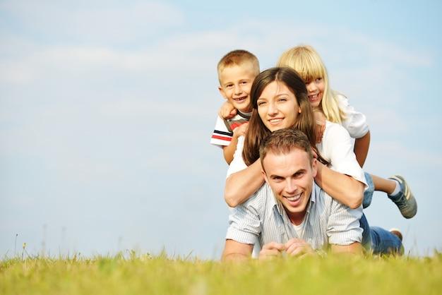 Familia feliz en el prado hermoso del verano que tiene tiempo feliz