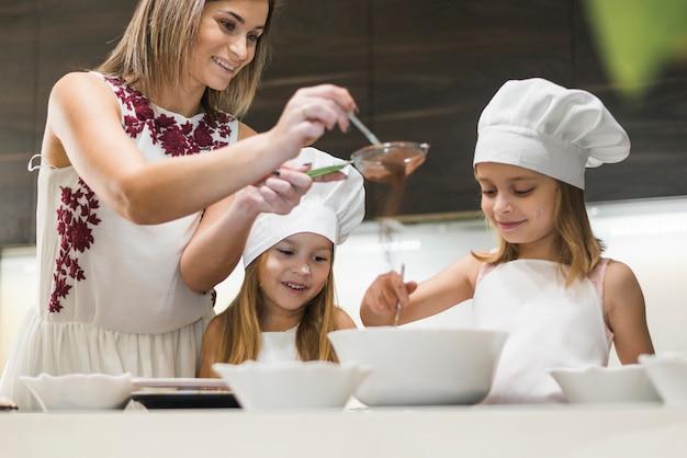 Familia feliz preparando comida mientras la madre tamiza polvo de cacao a través de un colador en la cocina