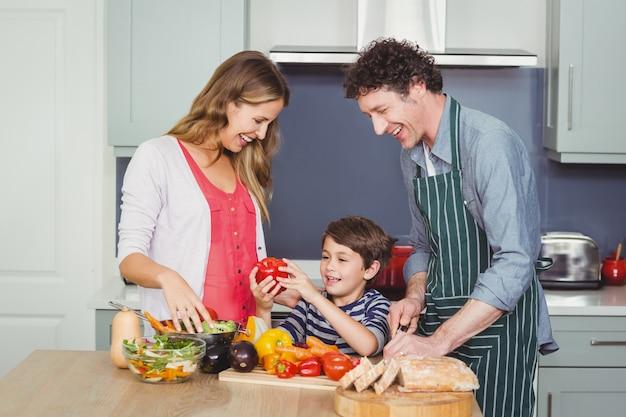 Familia feliz preparando una ensalada de verduras