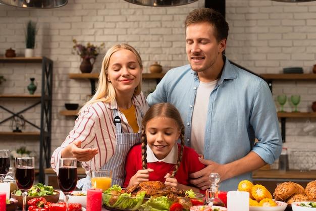 Familia feliz que huele el pavo fresco cocido