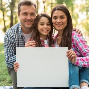 Familia feliz que lleva a cabo el cartel blanco en blanco en parque