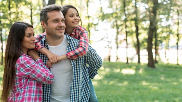 Familia feliz que lleva la camisa a cuadros del modelo que se coloca en el parque que mira lejos