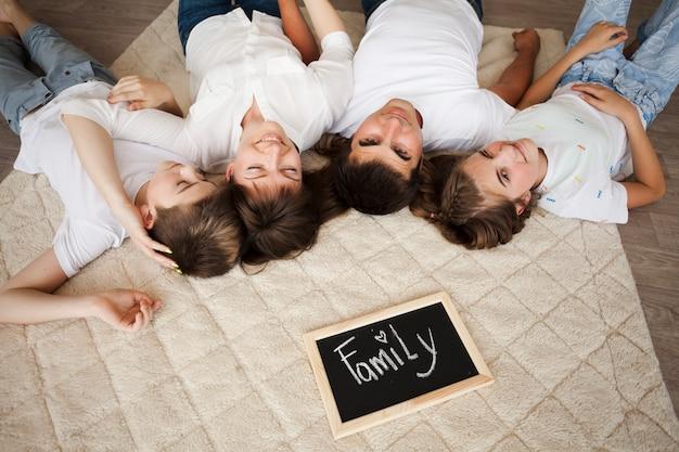 Familia feliz que miente en la alfombra cerca de la pizarra con el texto de la familia en casa