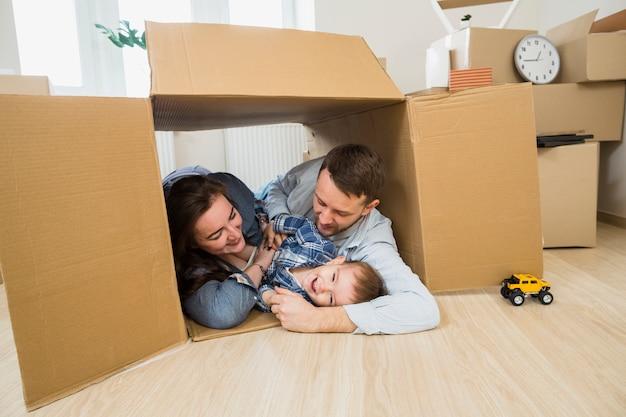 Familia feliz que miente dentro de la caja de cartón en casa