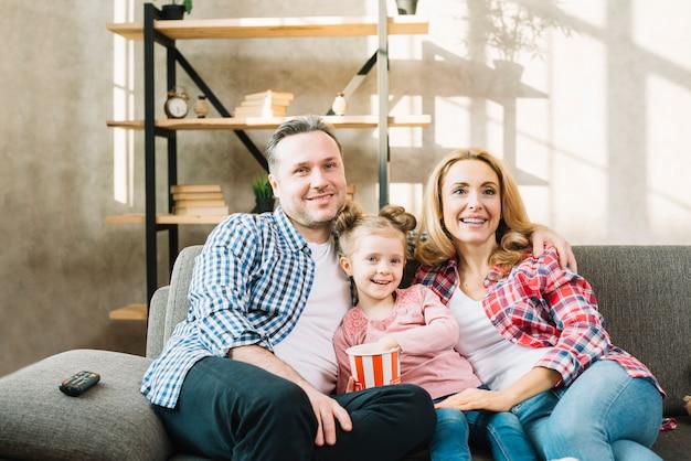 Familia feliz que ve la televisión con la hija que come palomitas de maíz en el sofá en casa