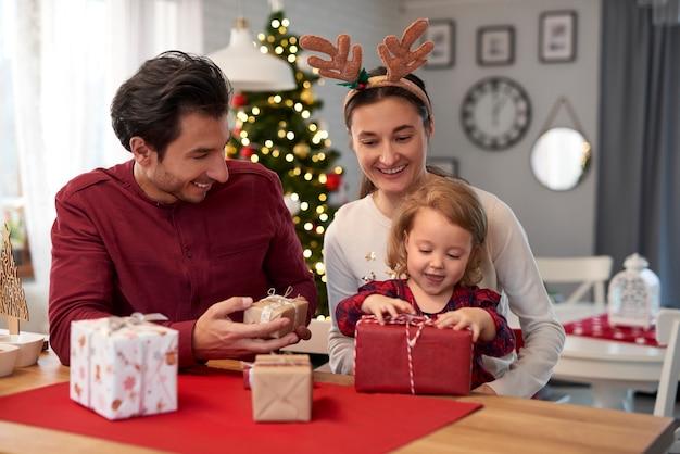 Familia feliz con regalos de navidad en casa