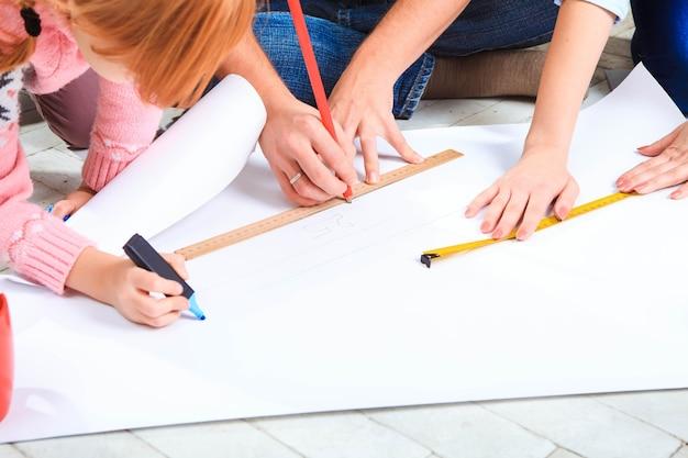 La familia feliz en reparación y reubicación. la familia planeando un alojamiento en un piso.