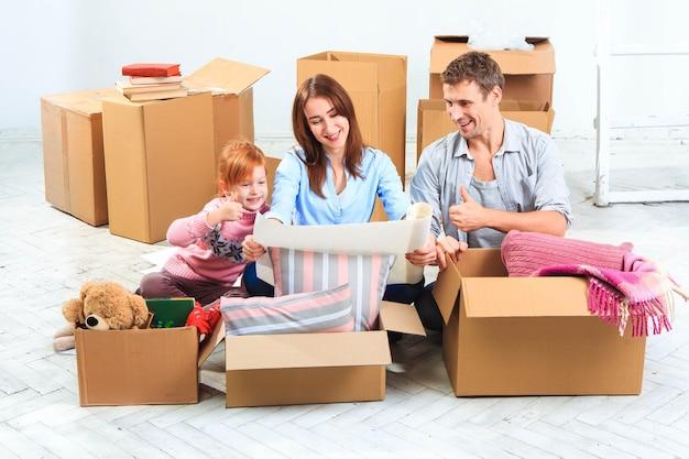 La familia feliz en reparación y reubicación la familia planeando un alojamiento
