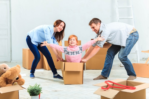 La familia feliz en reparación y reubicación sobre un fondo de cajas