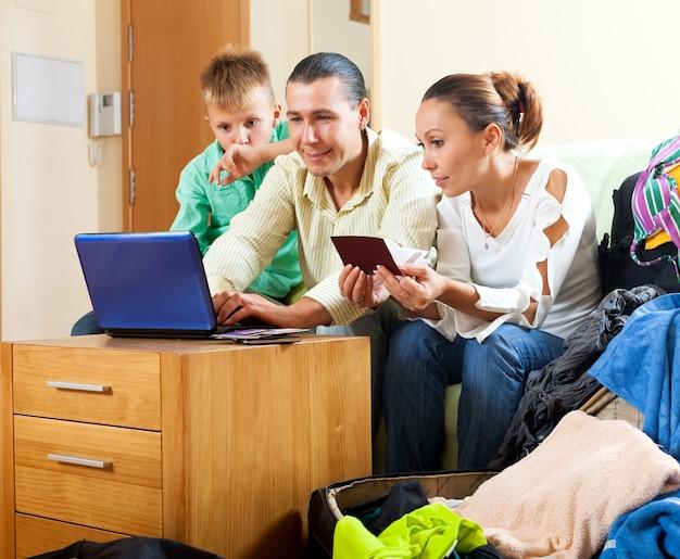 Familia feliz de reserva de tres hoteles en internet usando la computadora portátil