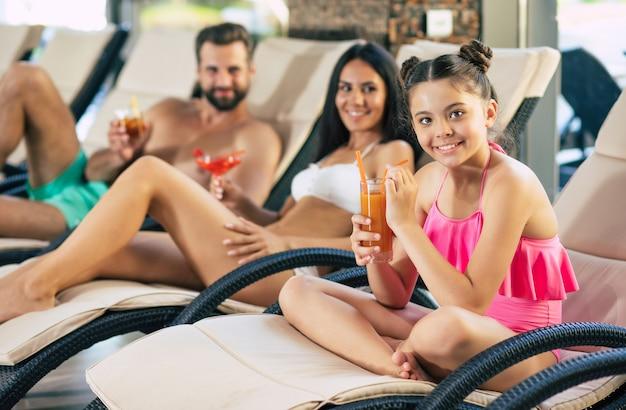 Familia feliz en el resort. padre guapo, madre hermosa y su hijita linda están tumbados en las tumbonas en el gran centro de spa con piscina y bebidas, jugos y cócteles