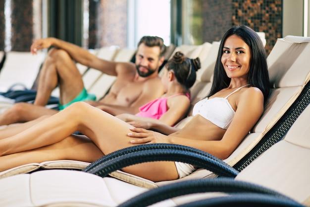 Familia feliz en el resort. padre guapo, madre hermosa y su hijita linda están tumbados en las tumbonas en el gran centro de spa con piscina. relájate de vacaciones