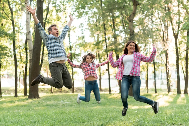 Familia feliz saltando en la naturaleza verde